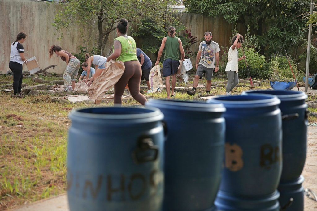 A row of blue plastic buckets. In the background, a group of nine people working in a yard (gardening, carrying boxes, picking up debris, etc.).