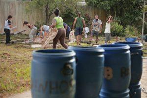 Plano aberto mostrando uma fileira de galões de plástico de cor azul, em primeiro plano e, ao fundo, um grupo de nove pessoas trabalhando em um quintal (carregando caixas, limpando etc).