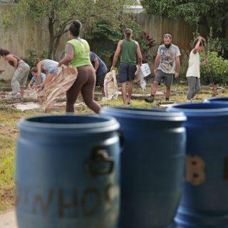 Plano abierto mostrando una fila de galones de plástico de color azul en primer plano y en el fondo, un grupo de nueve personas trabajando en un patio con pasto (cargando cajas, limpiando, etc.)