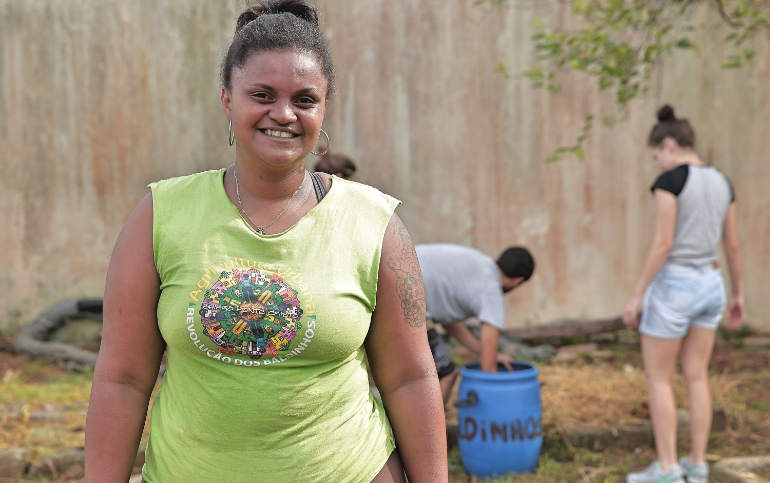 A black woman with her hair tied up. She is wearing a light-green tank top and smiling at the camera. In the background, two people are working in a garden.