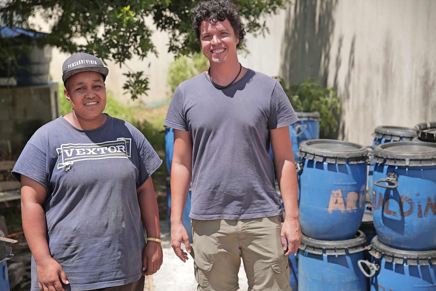 On the left side of the picture is a light-skinned black woman wearing a cap and a light purple t-shirt. She smiles at the camera. Next to her is a tall, thin, white man, with curly hair, also smiling at the camera. His t-shirt is the same color as hers. Beside him is a pile of blue buckets. In the background, some grass, and a tree. The leaves of the tree form shadows on a concrete wall.