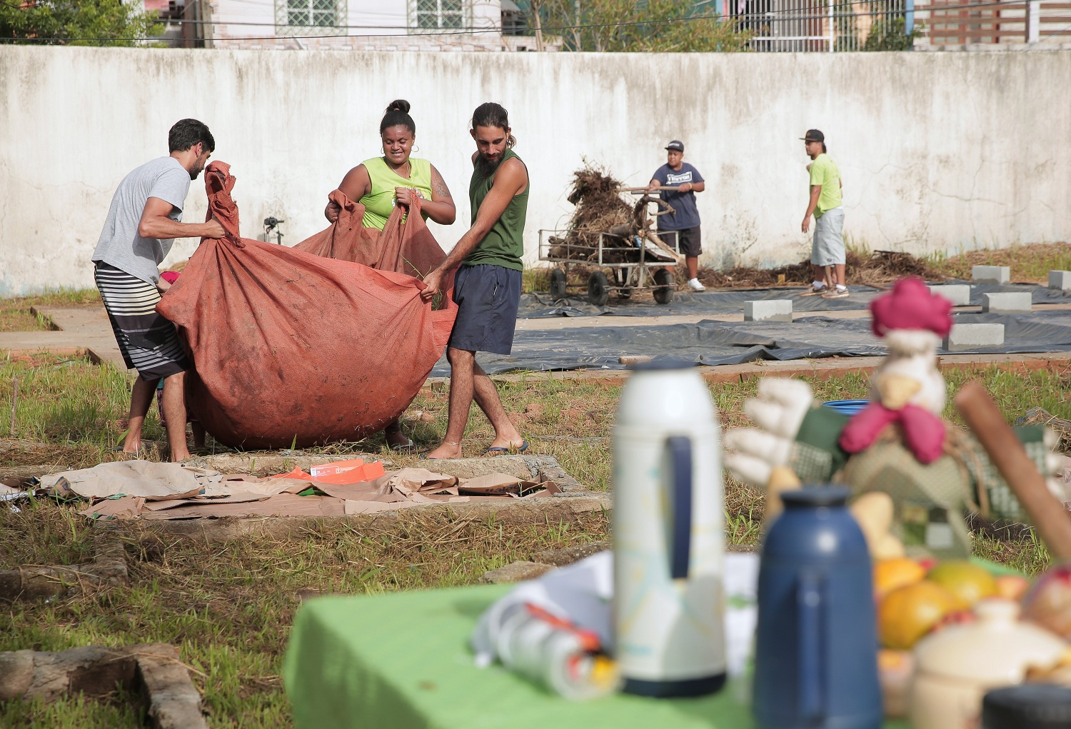 In the foreground is a table, slightly out of focus, with some food and thermos bottles. In the background is a group of 3 people carrying a tarpaulin with something inside it, presumably dirt. They are in a grassy yard. In the background is a concrete wall.