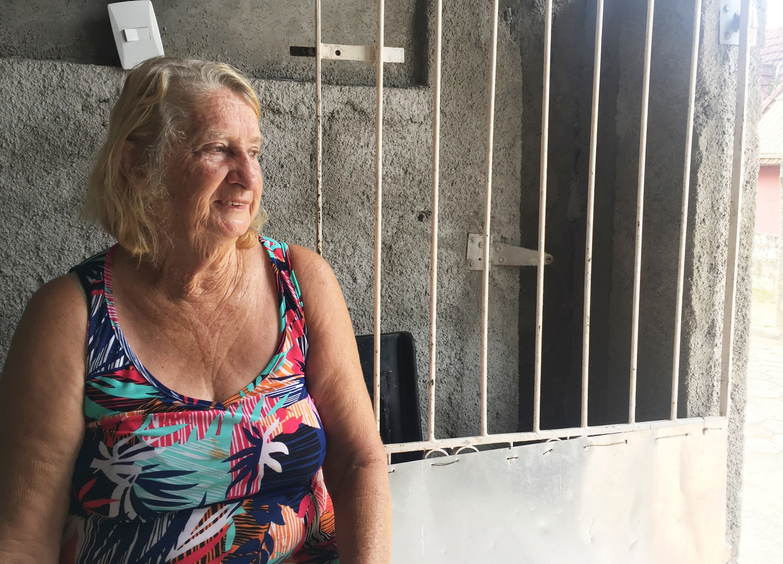 Uma mulher idosa, branca, cabelos claros (mistura loiro e grisalho), está sorrindo e olhando para o lado direito da imagem. Ao fundo, uma porta com grades. Uma luz/iluminação aparece do lado