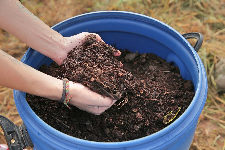 Plano fechado de duas mãos segurando um punhado de terra que está em um galão azul.