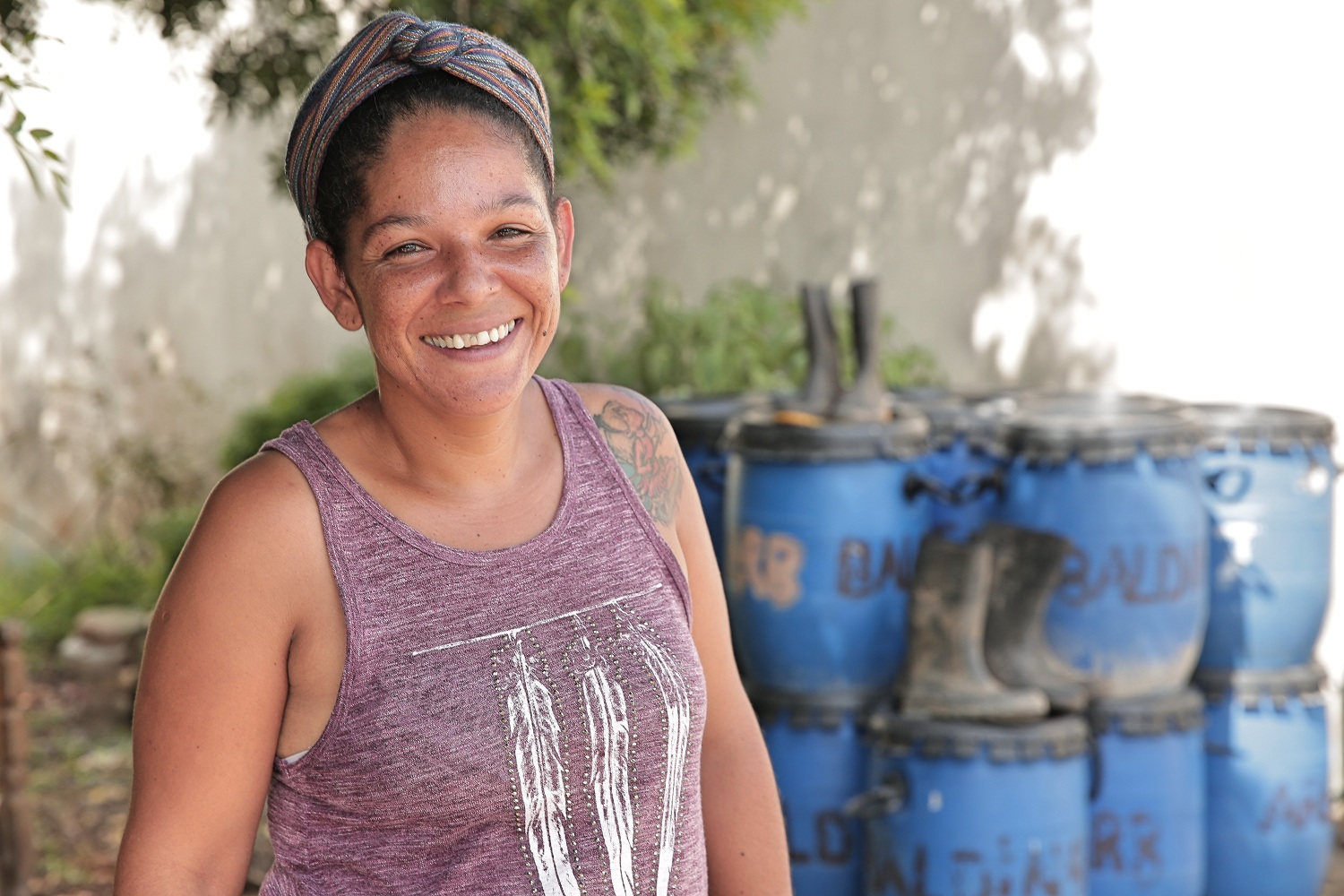 A light-skinned black woman with her hair is tied in a scarf. She is wearing a lavender tank top and smiling at the camera. In the background is a pile of blue buckets, out of focus. The sun is shining and trees cast shadows on a white wall behind the buckets.