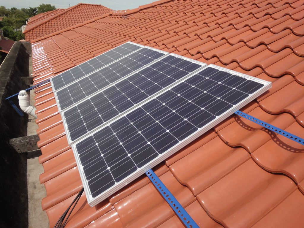 Photograph of a house with 10 rectangular photovoltaic panels covering part of its roof.