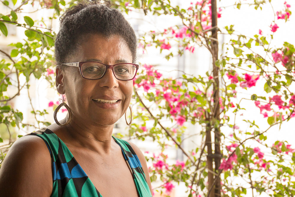 A black, middle-aged woman, shown from the bust up, wearing glasses and hoop earrings, with her hair tied back, looks at the camera and smiles. In the background, trees with pink flowers.