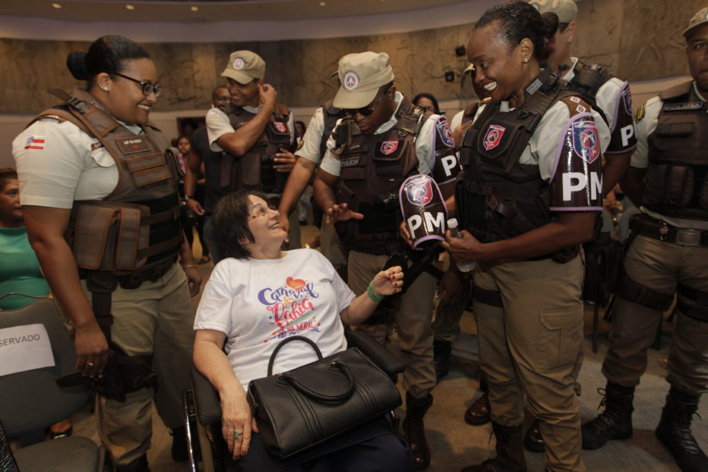 A group of policemen, all black men and women, stands around a white woman with short, dark hair who is in a wheelchair. She looks up slightly and smiles at a standing black woman, a police officer with her hair tied back, who is in uniform. They are smiling at each other.