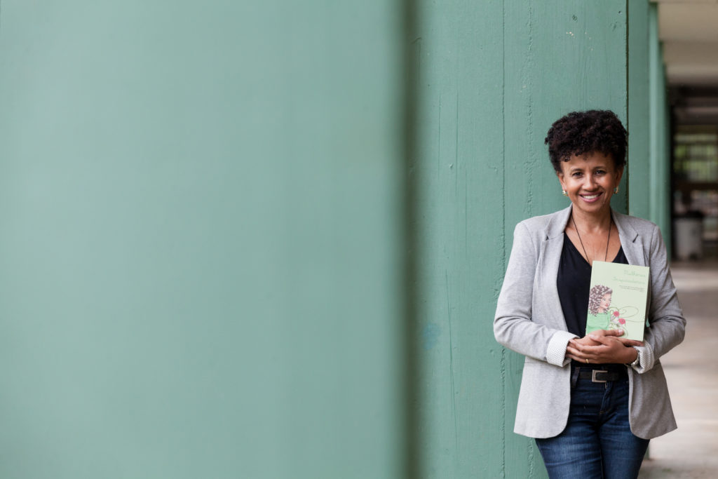 A black woman with short hair, wearing a black blouse, a gray blazer and jeans, smiles at the camera, holding a book in her hands. She is standing in a long corridor with a light green wall and concrete floor.