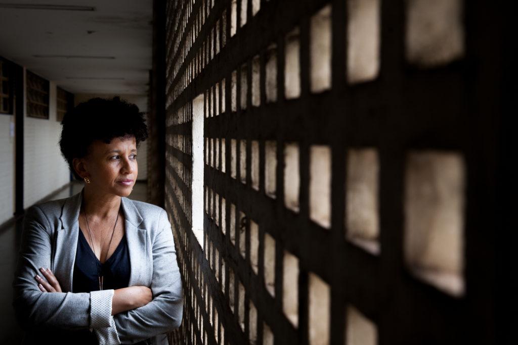 Mulher negra, cabelos encaracolados e curtos, usando uma camisa preta e blusa cinza está de braços cruzados olhando para para o lado direito da imagem, onde há uma parede vazada.