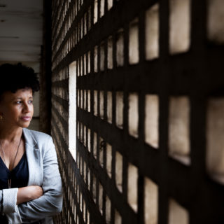 A black woman with short, curly hair, wearing a black shirt and a gray blouse stands, arms crossed, looking out the window. She stands next to a wall. In the background, the hallway is dim but light pours through many small windows in the wall.
