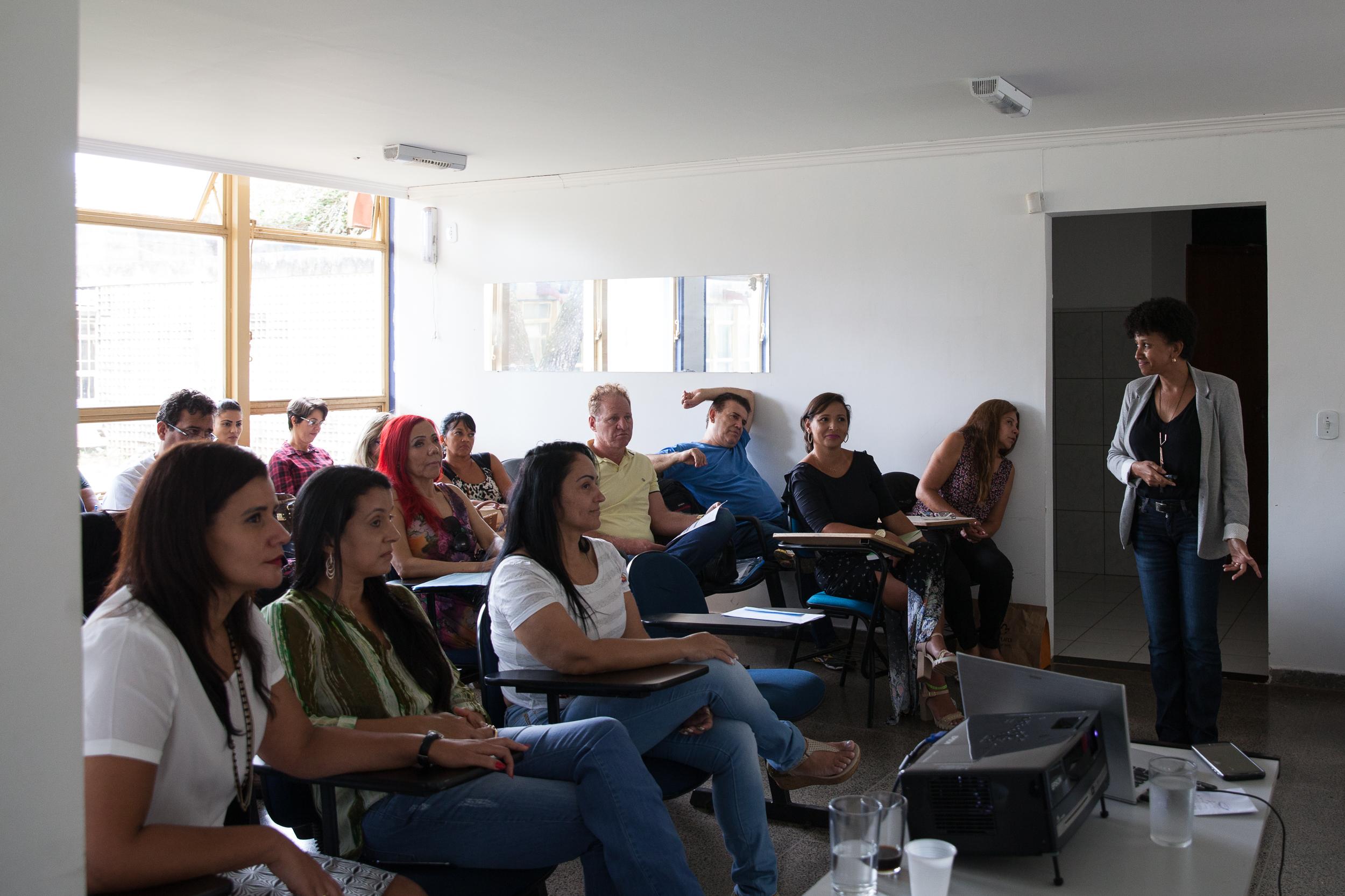 Mulher negra de cabelos curtos e encaracolados, usando calça jeans, tayer cinza e camisa preta, está caminhando e gesticulando na frente de uma turma de pessoas adultas, todas sentadas, que assistem à sua aula.