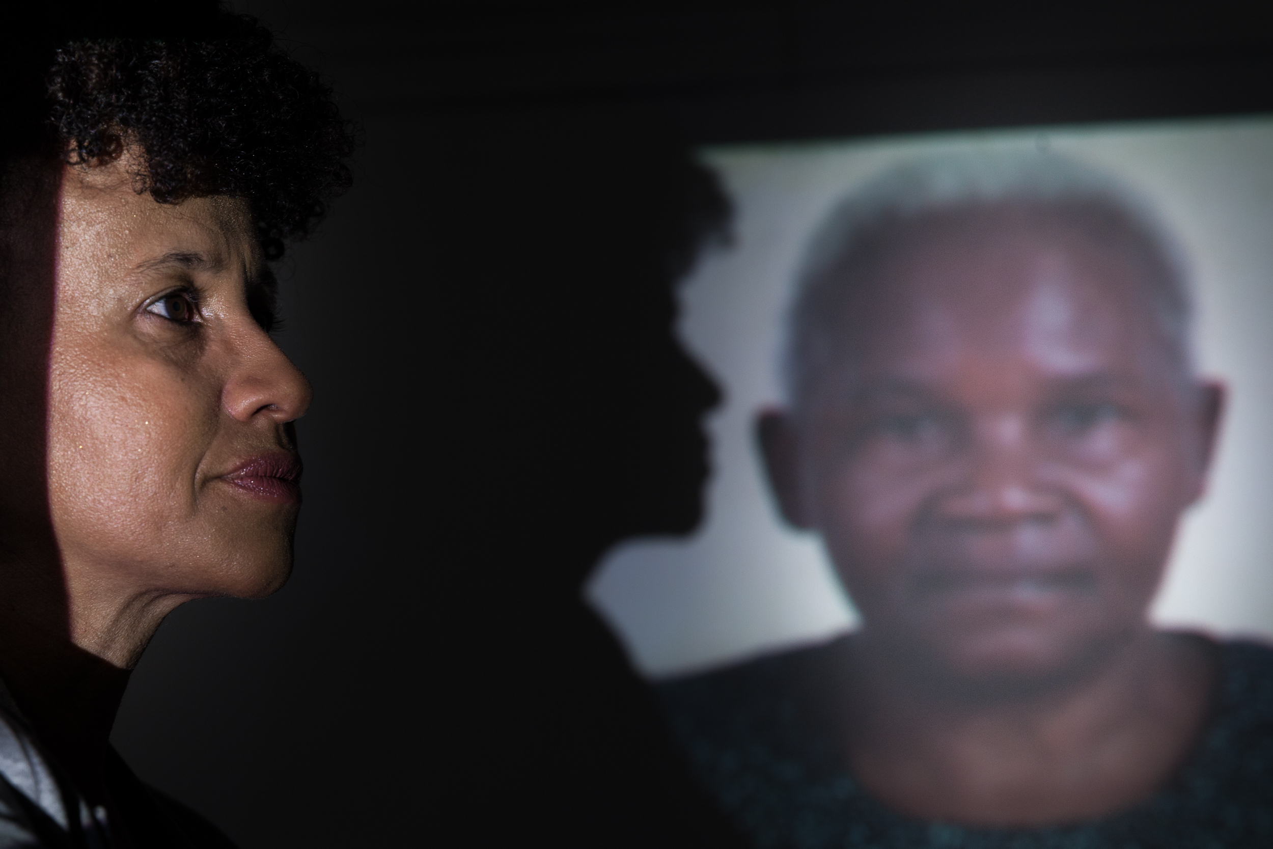 A projected photo of a black woman with short, white hair. On this projected photo, another woman's shadow appears. In the foreground is the woman casting the shadow, standing in profile: a black woman with short, curly black hair.