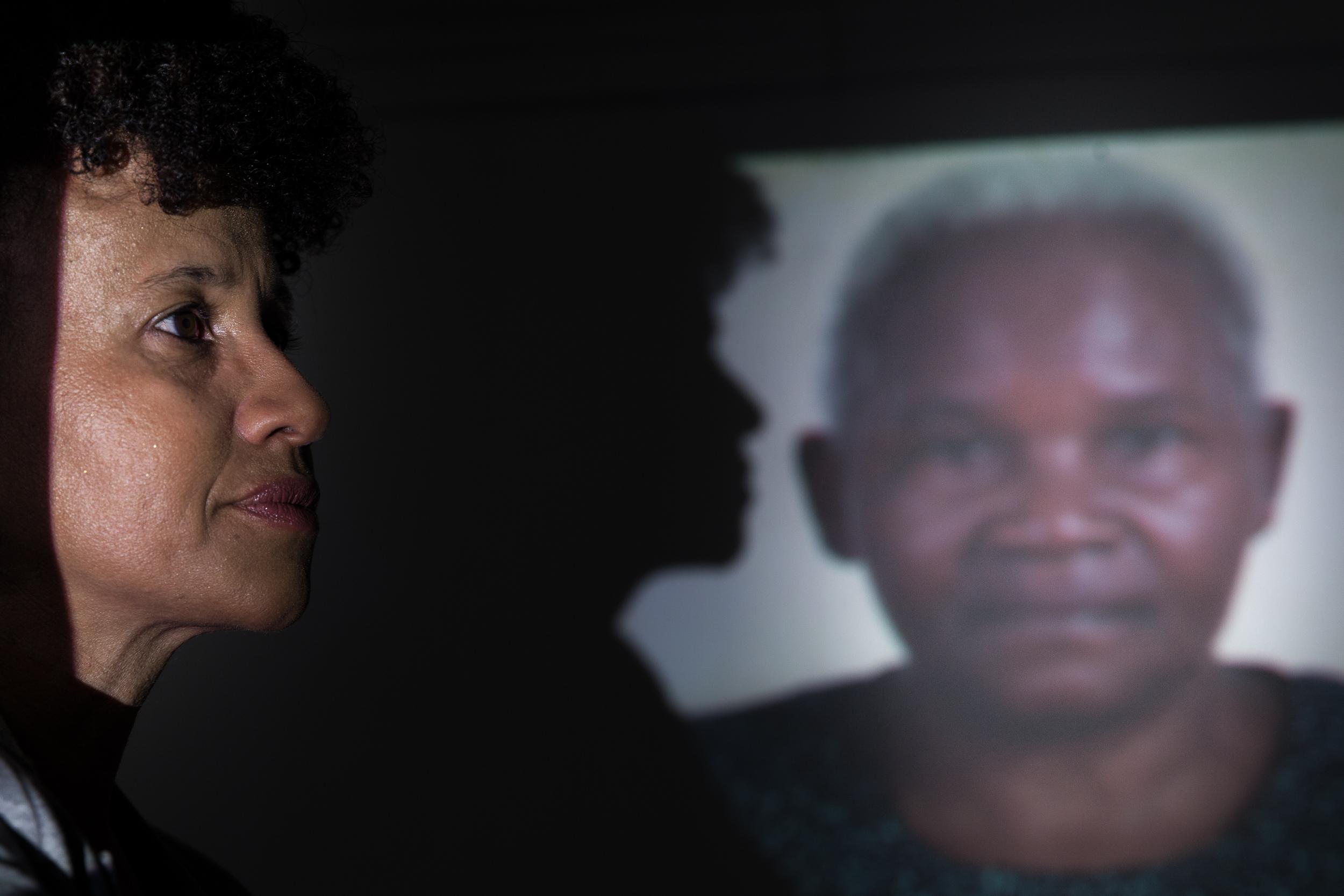No fundo da imagem, uma projeção da foto de um pessoa negra, de meia idade, cabelos brancos - do lado esquerdo da imagem, aparece a sombra de uma mulher negra de cabelos curtos (Gina Ponte), que aparece em primeiro plano na imagem.