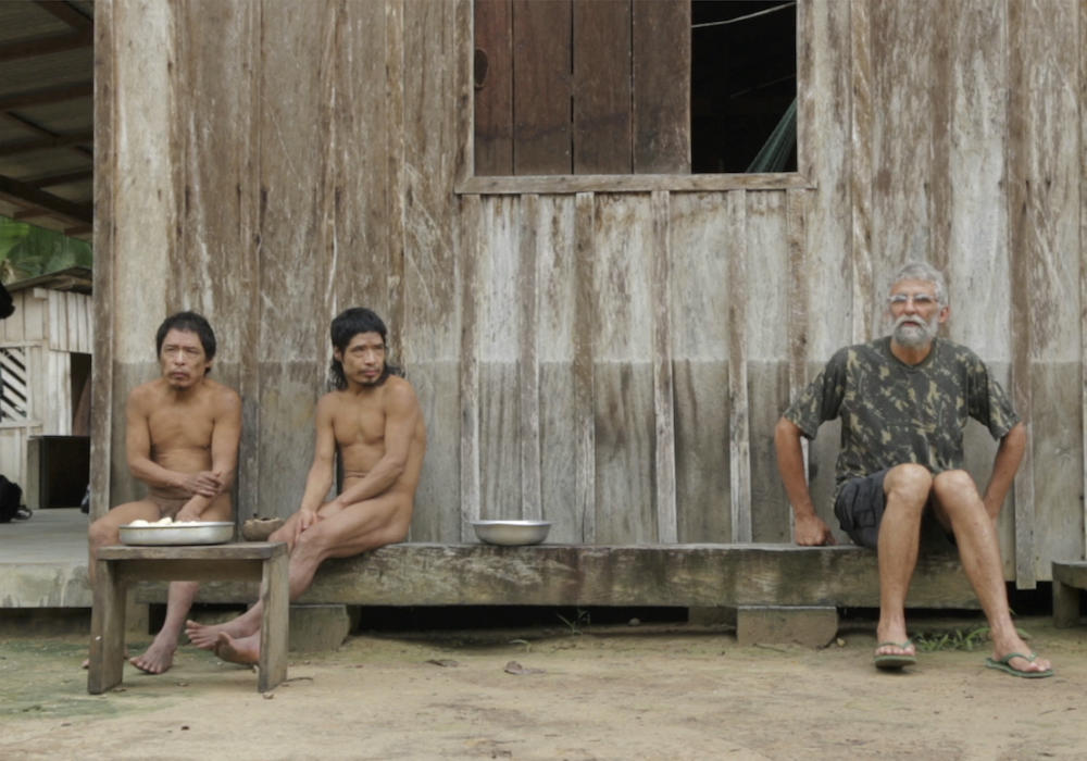In the lower left corner of the picture, two short, naked, brown-skinned men sit in front of a wooden house, on a wooden bench. One looks ahead, into the distance, while the other looks to the right side of the picture, where, on the other end of the bench, a tall, white man with gray hair and beard is also seated. The tall man is wearing glasses, a camouflage T-shirt and gray shorts. He looks ahead, into the distance.