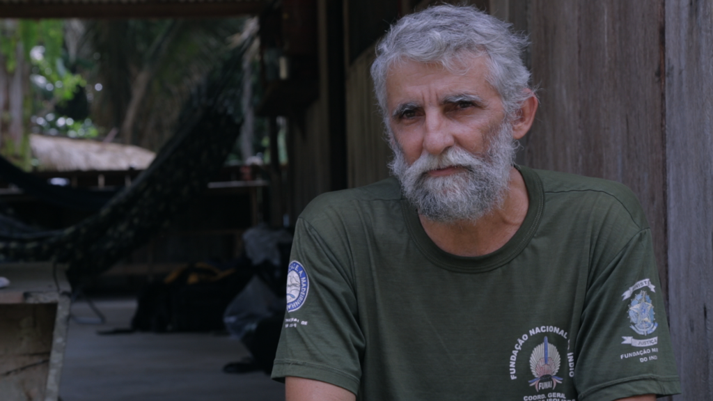 A man with gray hair and a beard, wearing a dark green t-shirt, looks at the camera. In the background is a wooden house and some of its interior.