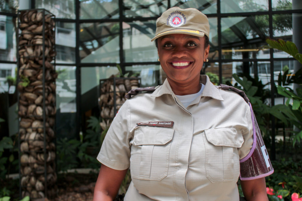 A black woman, her hair tied back, wearing a beige police uniform (a beige cap and matching jacket). She smiles at the camera.