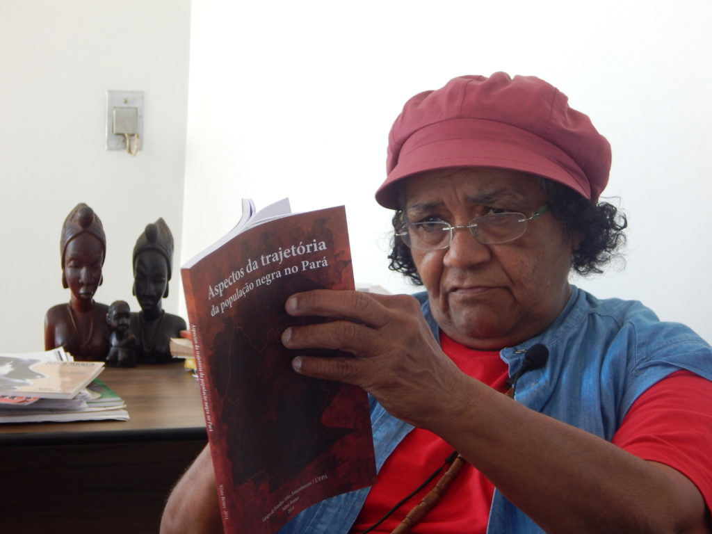 "A black woman with short curly hair is wearing glasses, a burgundy beret, and a blue T-shirt covered by a denim vest. She is seated, holding a partly-open book titled, in Portuguese, ""Aspects of the Trajectory of the Black Population in Pará."" Behind her are several busts of black women on a wooden table, and a stack of what appear to be books, magazines or pamphlets."