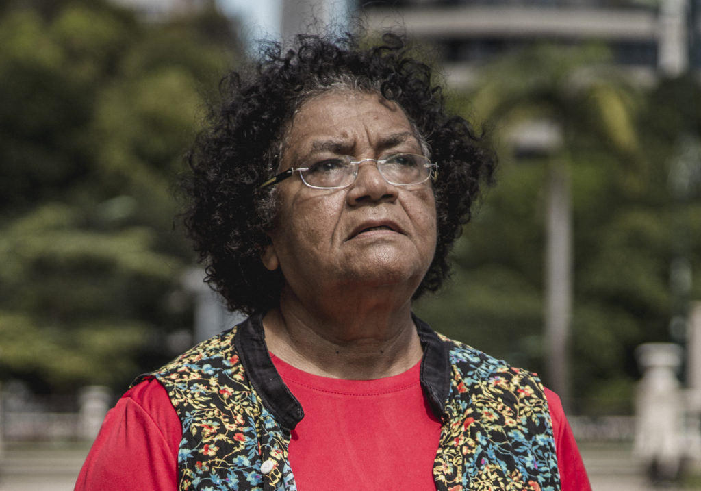 An elderly black woman with short curly hair, wearing glasses, a red T-shirt and a colorful, flowered vest, shown from the bust up. She is looking up slightly. The background, trees and concrete buildings, is out of focus.