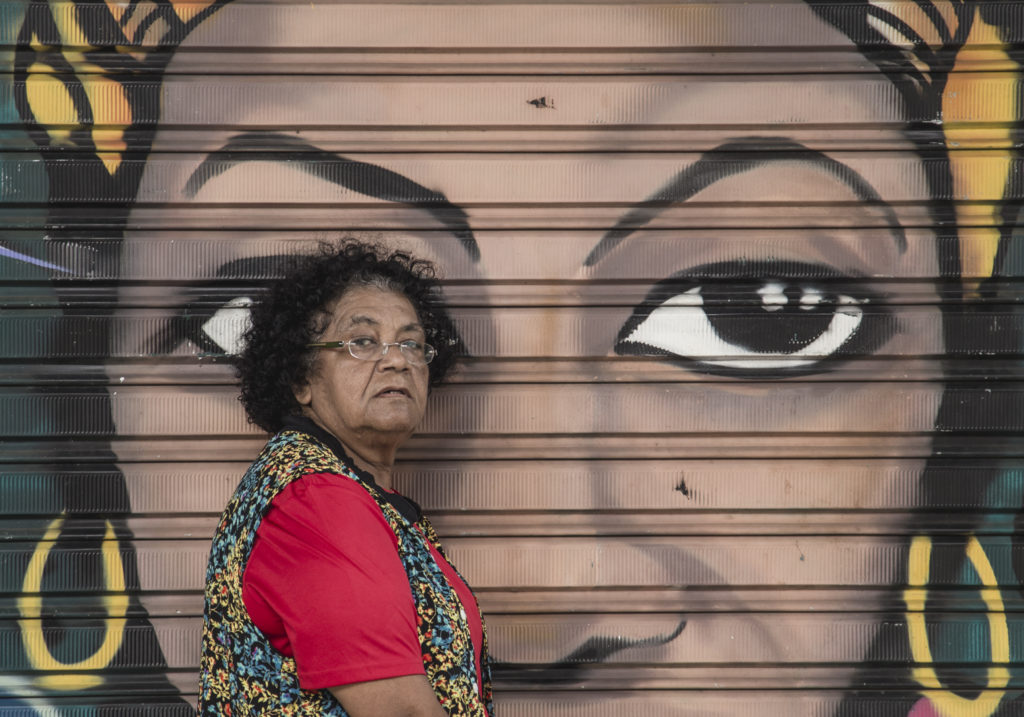 A black woman with curly hair, turned sideways. She is wearing glasses, a red shirt and a colorful, flowered vest. She is looking at the camera without smiling. Behind her, a mural depicting the face of a black woman with big eyes.