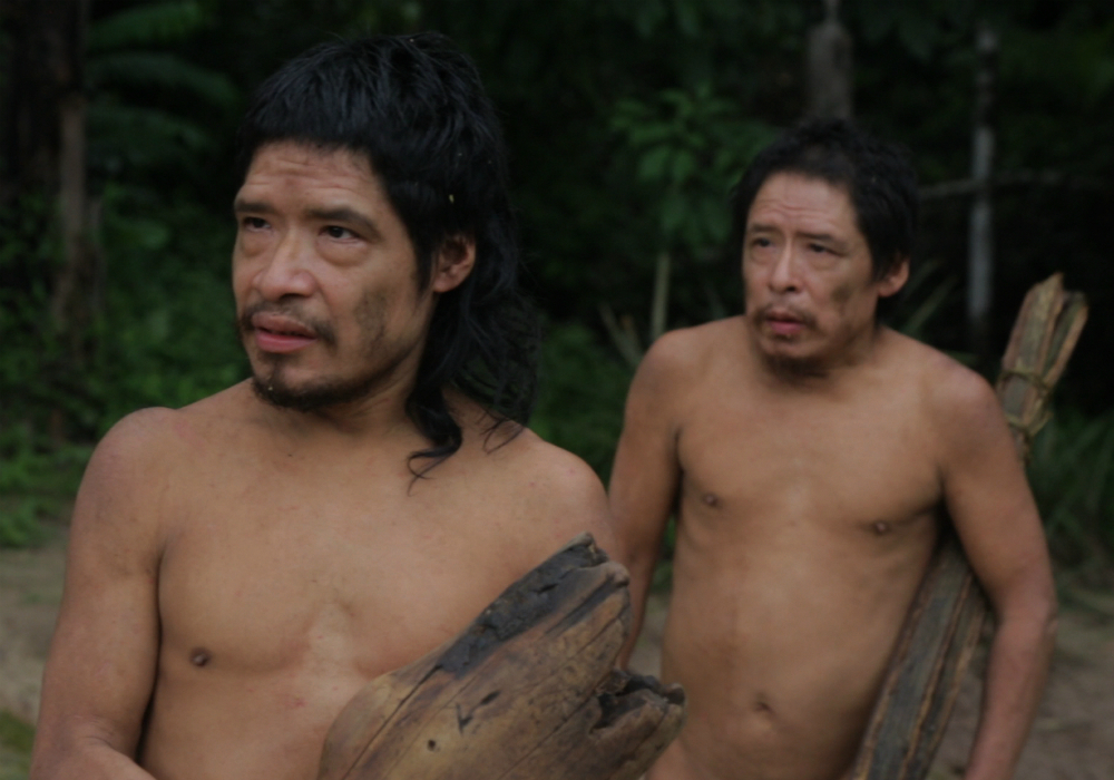 Two short, brown-skinned, shirtless men (shown from the waist up) are looking to their right. The first man, in front of his companion, has straight, black, shoulder-length hair and a slight beard and mustache. The second man looks a little like the first one but seems to be older and with shorter hair. Both are carrying firewood.