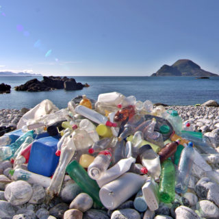 Plastic bottles and other plastic waste are piled up on white stones on a rocky beach, with the sea and a small island in the background.