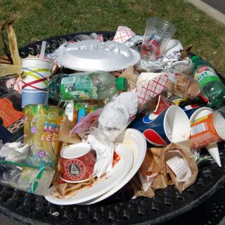 Uma cesta de lixo com vários copos, garrafas e embalagens plásticas. A cesta de lixo parece estar em uma rua asfaltada e parte de um canteiro com grama aparece atrás.