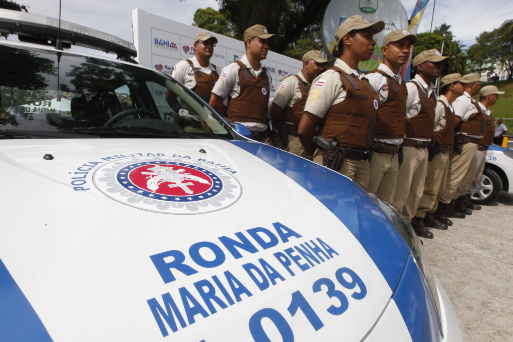 "In the foreground, the hood of a police car, bearing the police force's coat of arms. On the hood are the words, ""Ronda Maria da Penha 0139."" In the background, a group of more than 10 police officers is lined up in 3 horizontal rows, standing at attention. They are all wearing dark brown vests, with beige pants and matching beige caps."