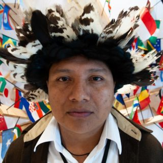 An indigenous man, 32 years old, with dark skin and black eyes, wearing a headdress made of white and black feathers, looks at the camera without smiling. Behind him are small flags from various countries hanging from a wall. The photo shows the man only from the chest up.