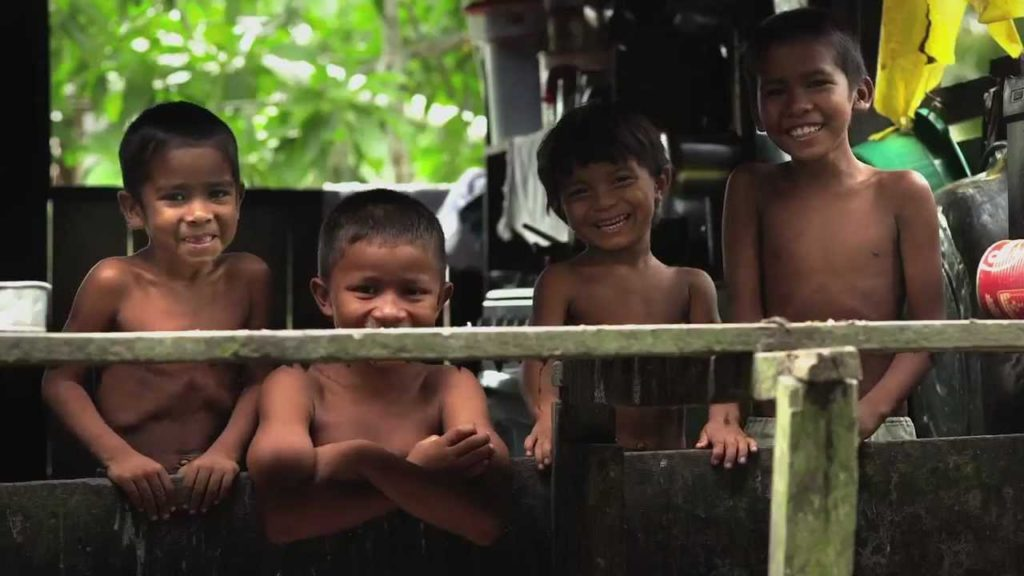 Four shirtless indigenous children, appearing to be between 5 and 7 years old, stand next to each other and smile to the camera. They are behind a wooden fence, appearing only from the waste up.
