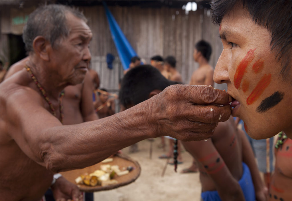 In the left corner of the image, an elderly indigenous man, shirtless and wearing a colorful bead necklace, looks to the right side of the image as he uses his right hand to put food in the mouth of another indigenous man. This man is younger, with his face painted in red and black stripes. In the back are other indigenous men, out of focus.