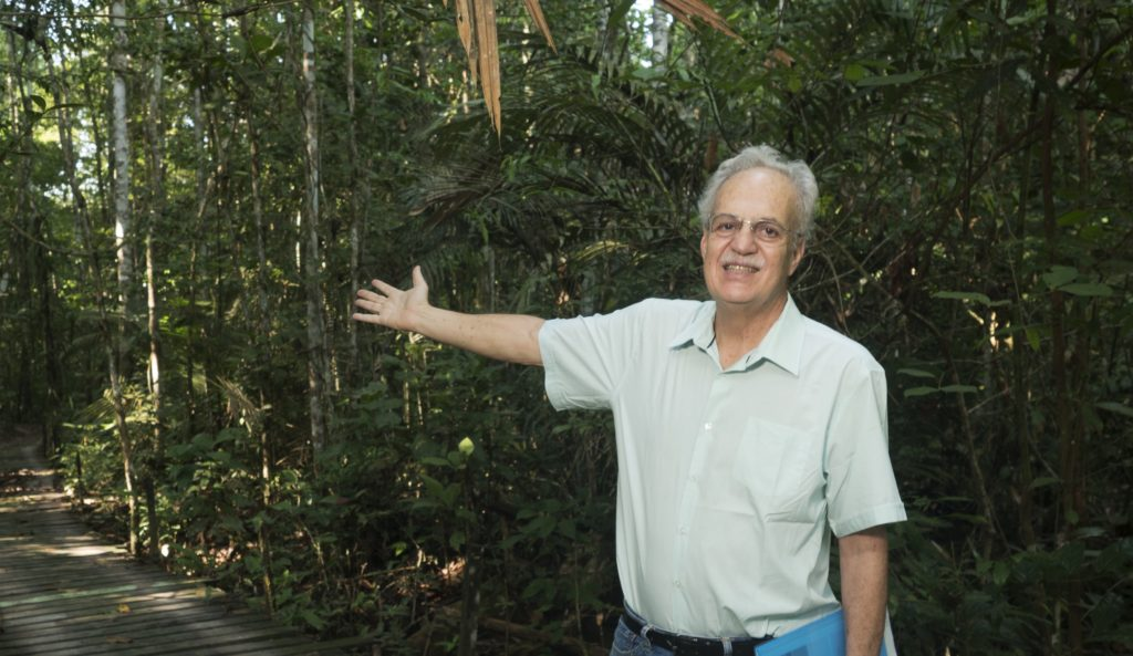 The same white-haired 66-year-old man from the previous photo is wearing glasses and a light blue shirt. His right arm is outstretched, his hand pointing to the forest behind him. In his left hand, he holds a blue folder.