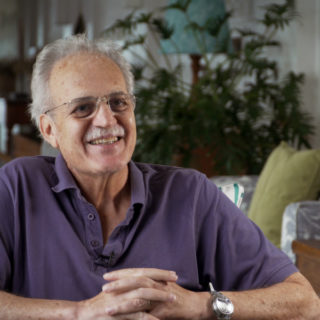 A 66-year-old man with a mustache and white hair, a bit bald. He wears glasses and a short-sleeved purple polo shirt. His forearm is resting on a table and his hands are clasped together. He smiles, looking to his left. In the background is a living room with a sofa, a large wooden table and a large, leafy green plant.