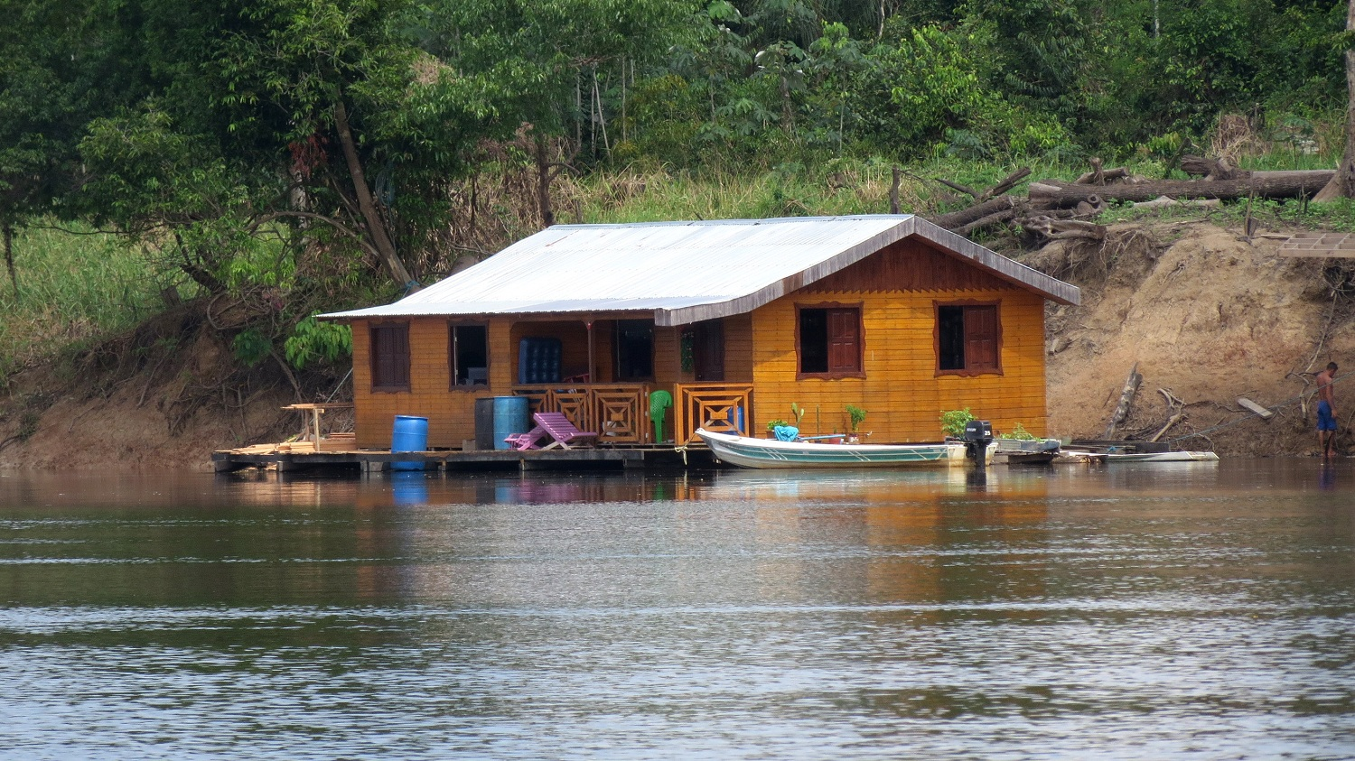 A wooden house, with a veranda, on the river. A canoe is anchored at its side.
