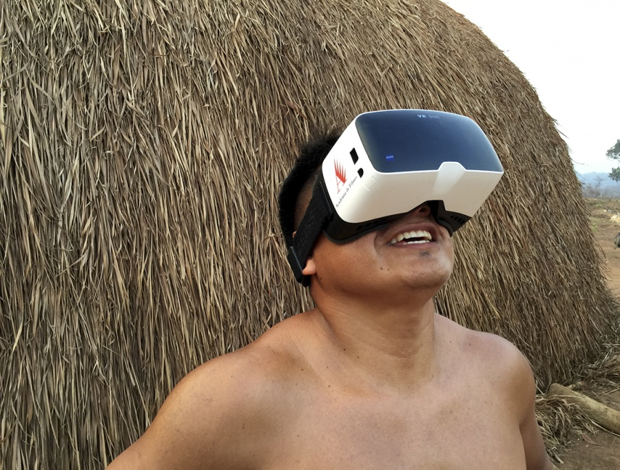 A brown man with short, dark hair is wearing, tied around his head, a virtual reality headset, which has a white plastic base, with a large dark lens covering his eyes and nose. Head lifted slightly, he smiles. Behind him is a straw hut, only partly shown.