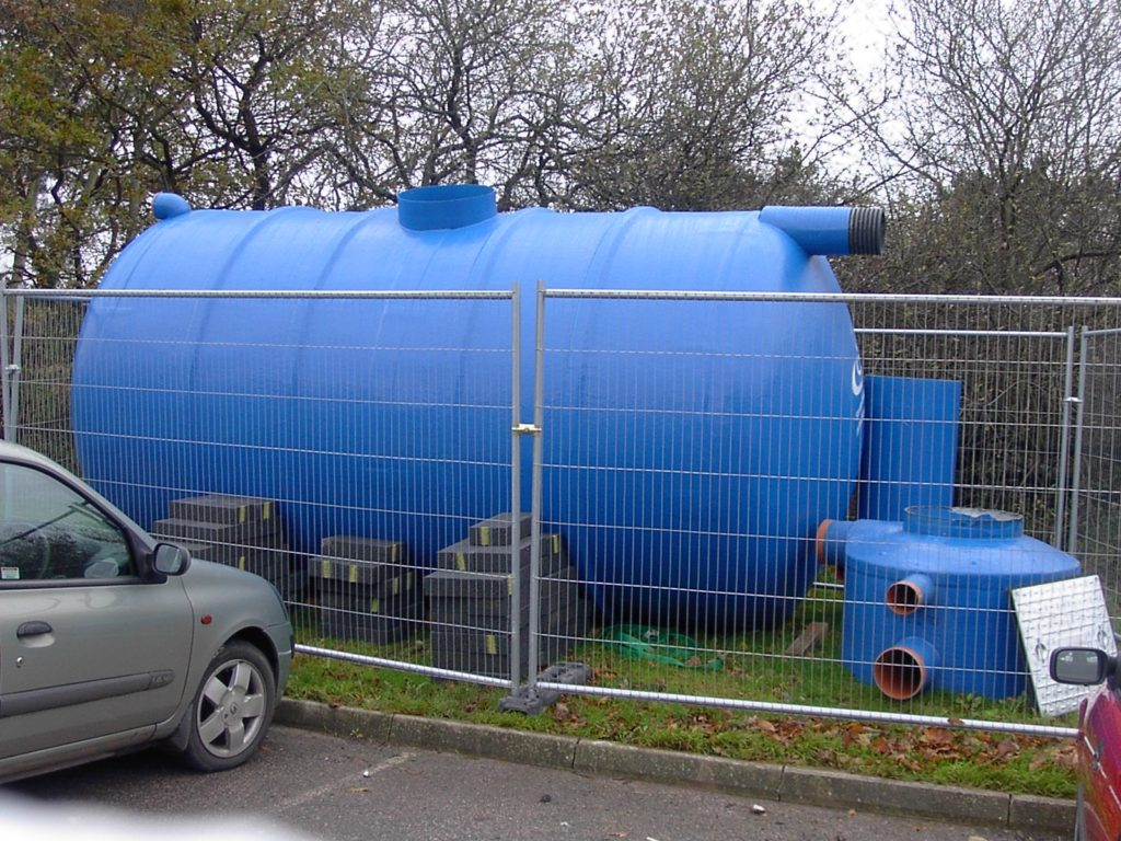 On a lawn, behind a fence, is a blue, plastic, cylindrical tank with some cinderblocks stacked against its side to stabilize it. Next to the tank are other plastic parts apparently not in use at present. In the foreground, in the left corner of the photo, is a parked car. The tank is much larger than the car.