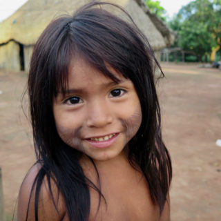 An indigenous girl, who looks about 7 years old, with big black eyes and straight black hair down to her chest. She is looking at the camera and smiling slightly. The lower halves of both of her cheeks are painted with black stripes. Behind her, shown only partially, is a wooden house with a thatched roof.