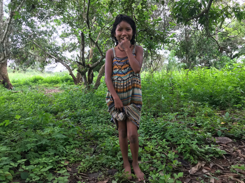 An indigenous girl, who looks about 10 years old, wearing a colorful printed dress. She is holding the tip of her dress in her left hand, and puts her right hand to her mouth as she smiles. She is standing in the middle of a forest.