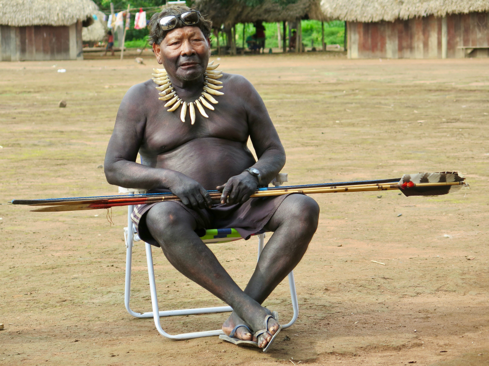 An indigenous man with short black hair, shirtless and wearing only green shorts, with his full body painted black from the nose down. He is sitting on a beach chair, with sunglasses resting on his head and holding a bamboo spear with a feather on its tip. The chair is on dirt ground, and behind him we see parts of a small wooden house with a thatch roof.