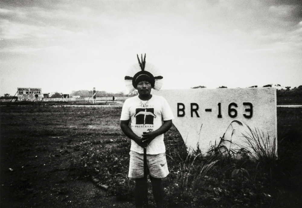 "Black and white photo of an indigenous man, wearing a feather headdress, jean shorts and a white t-shirt, posing in front of a sign that reads ""BR-163."""