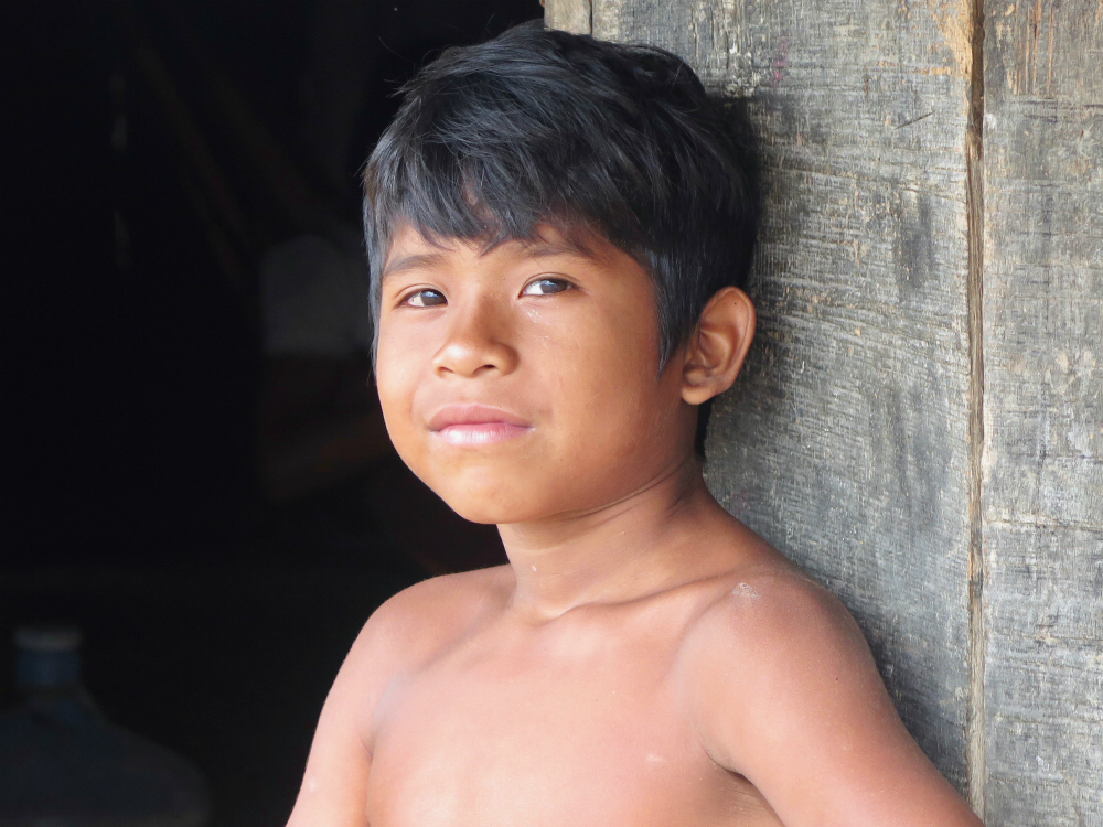 A dark skinned indigenous boy, with short black hair and brown eyes, shirtless, is resting against a wooden wall. He is looking straight at the camera.
