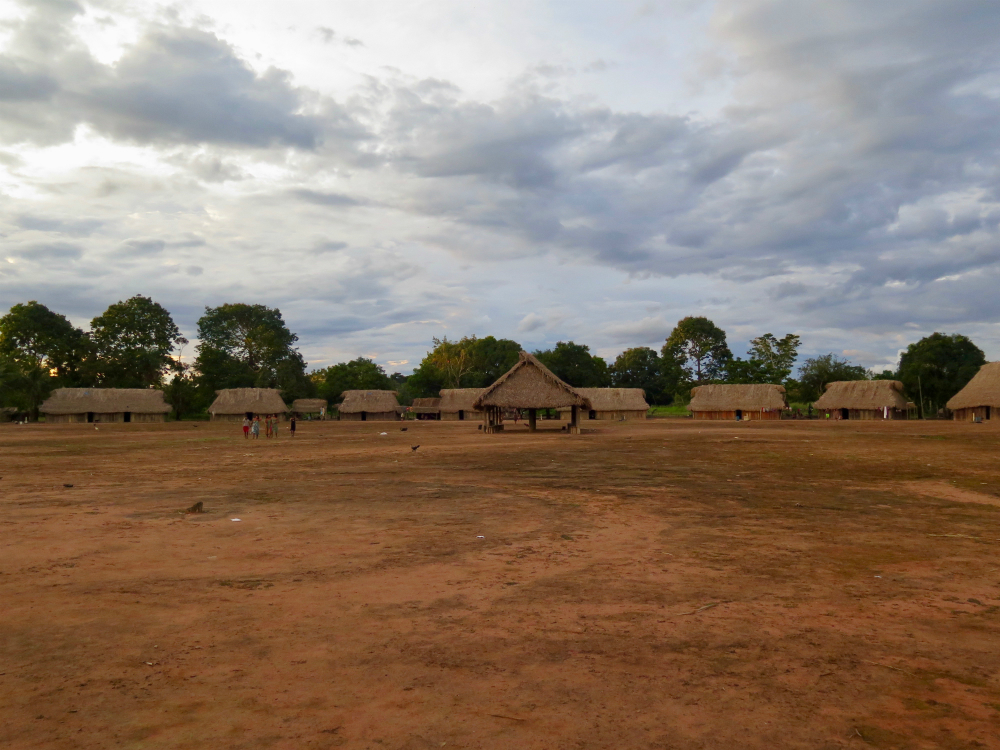 Wide shot of an indigenous village. In the photo is the dirt ground, a set of approximately 10 houses built of wood with thatch roof and, in the center, an open structure supported by wooden pillars with a thatch roof. Behind the houses are some trees, and the sky is blue with some clouds.