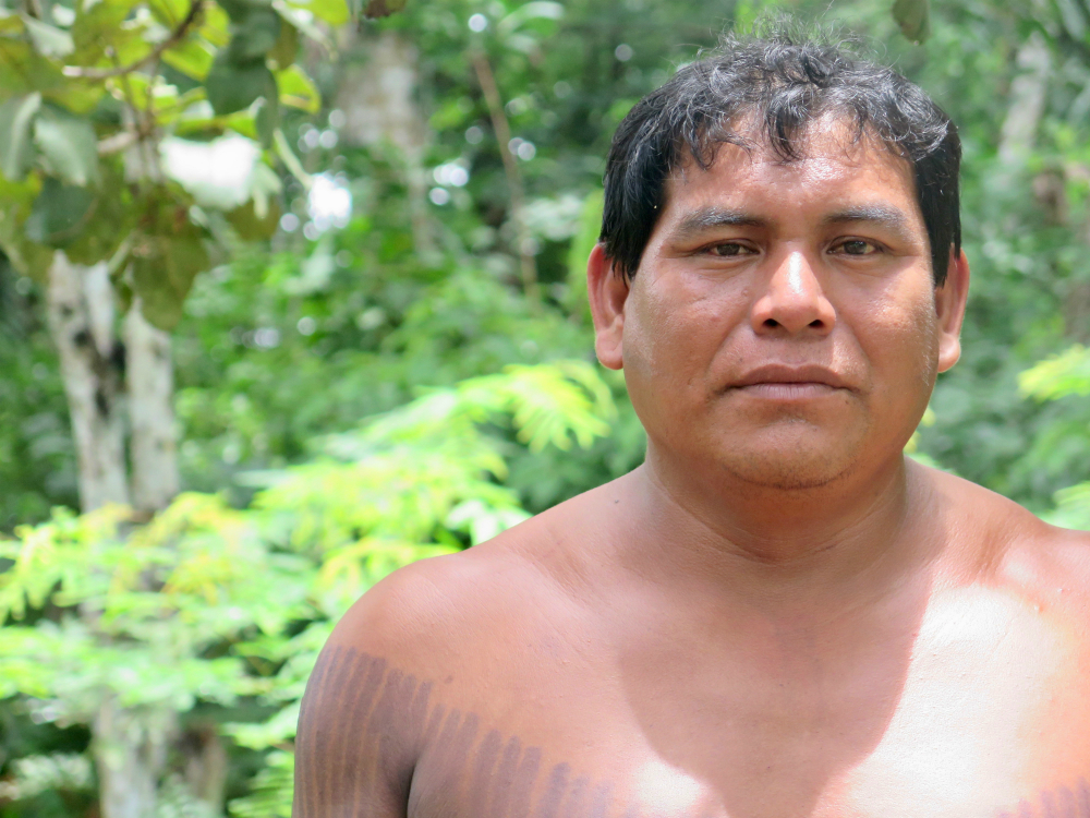 A man, seemingly between 30 and 40 years old, with dark skin, short hair, shirtless and with part of his chest painted with black stripes. He looks at the camera without smiling. Behind him are some trees out of focus.