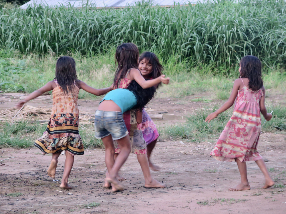 Five indigenous children wearing floral print dresses, playing, running and hugging each other.