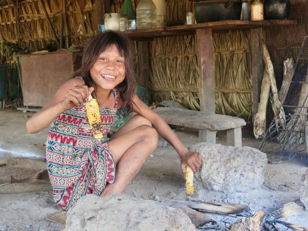 Uma menina indígena, usando vestido estampado colorido, segura uma espiga de milho com a mão direita, e a mostra para a câmera enquanto sorri. A outra mão segura uma espiga de milho perto de uma pequena fogueira. Ela está dentro de uma casa com paredes de palha, móveis simples de madeira (mesa, banco) e algumas pedras