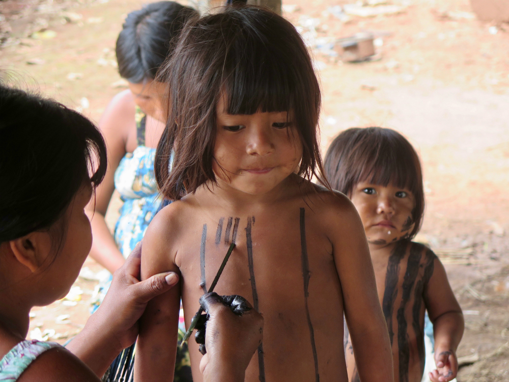 An indigenous woman (with her back to the camera, in the left corner of the picture) paints on the body of an indigenous child with straight black hair and a serious expression. The woman, holding a thin stick, is drawing vertical black lines on the child's chest.
