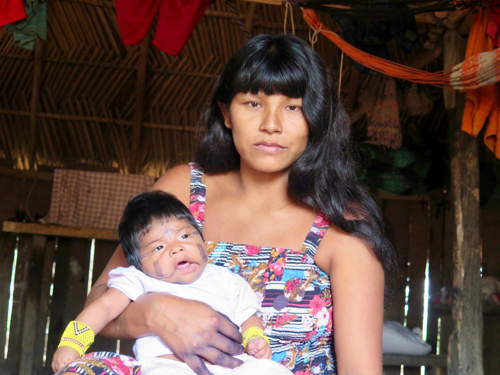 Imagem de uma jovem mulher indígena, com cabelos longos e negros, com franja, segurando um bebê indígena no colo. Ela olha para a câmera, sem sorrir. O bebê é gordinho, tem as bochechas pintadas de preto, e usa pulseiras com miçangas amarelas.