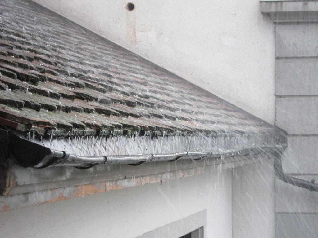 Imagen de un techo, sobre el cual cae lluvia y granizo. El agua es recogida por un canal.