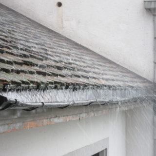 Picture of a roof, on which rain and hail falls. The water is collected by a gutter.