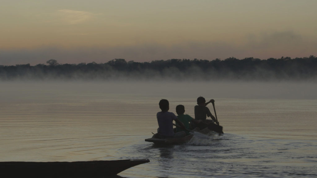 Photo of a silhouette of three boys in a canoe, paddling in a river towards a forest. The photo seems to have been taken at sunset.